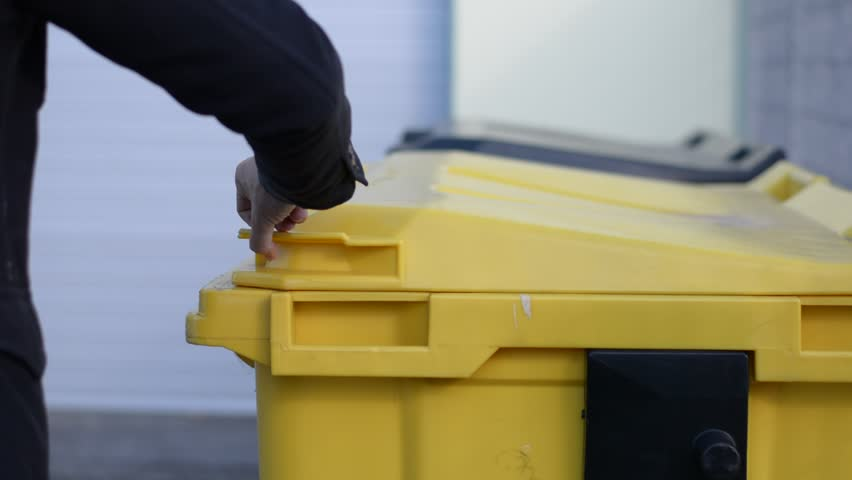 Hand of man throwing away small cardboard box in big waste container for recycling