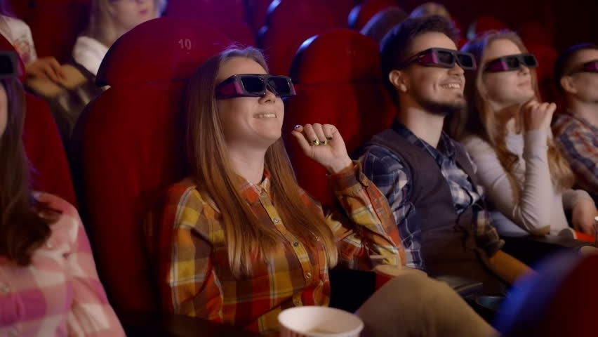 Young people watch movies in cinema, Watch a comedy in 3D, all smiling and eating popcorn.