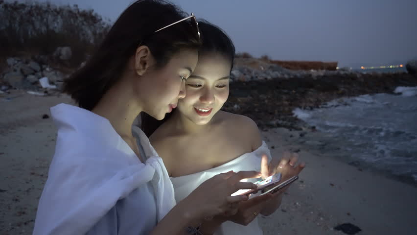 Two women stand play the phone at night. Technology concepts can communicate anywhere.   Shutterstock HD Video #26338004