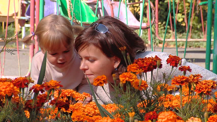 Mum and the daughter look at flowers