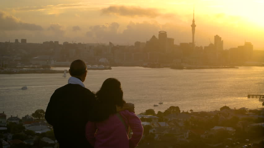 Senior couple watching sunset in Auckland city from mount Victoria in Devonport, Auckland, New Zealand. Sightseeing point, travel attraction.