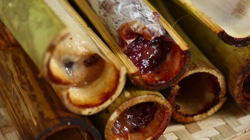Burned sticky rice with sweet coconut milk in bamboo shot. Khao Lam is Thai dessert, selective focus. | Shutterstock HD Video #26404409