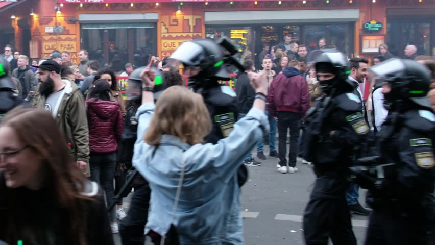 """Berlin, germany - may 01, 2017: Girl showing middle finger to riot police during the """"Revolutionary May 1st Demonstration"""" on labor day in Berlin, Kreuzberg."""