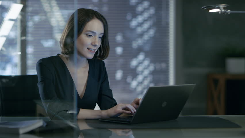 Female Executive Works on a Laptop in Her Private Office with Big City View. She's Laughing Charmingly. Her Workspace is Done in Dark Overtones. Shot on RED EPIC-W 8K Helium Cinema Camera. Royalty-Free Stock Footage #26431907