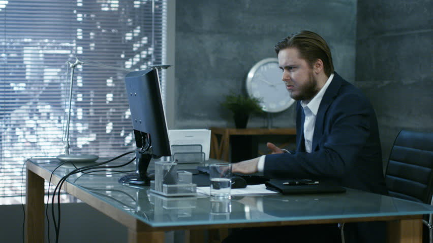 In a Private Office Businessman Loses Temper and Hits His Monitor With Keyboard, in an Act of a Rage Throws everything off the Table. Shot on RED EPIC-W 8K Helium Cinema Camera. Royalty-Free Stock Footage #26432087