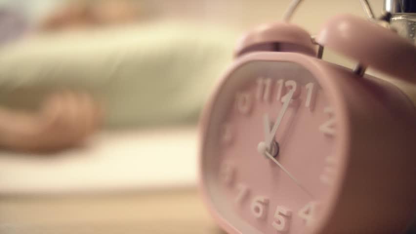 Romantic alarm clock and flowers on bedside table. Alarm Clock and Reading Lamp on Bedside Table. Vintage metal analog alarm clock with Arabic numbers and wind-up mechanism. Retro look pine bedroom