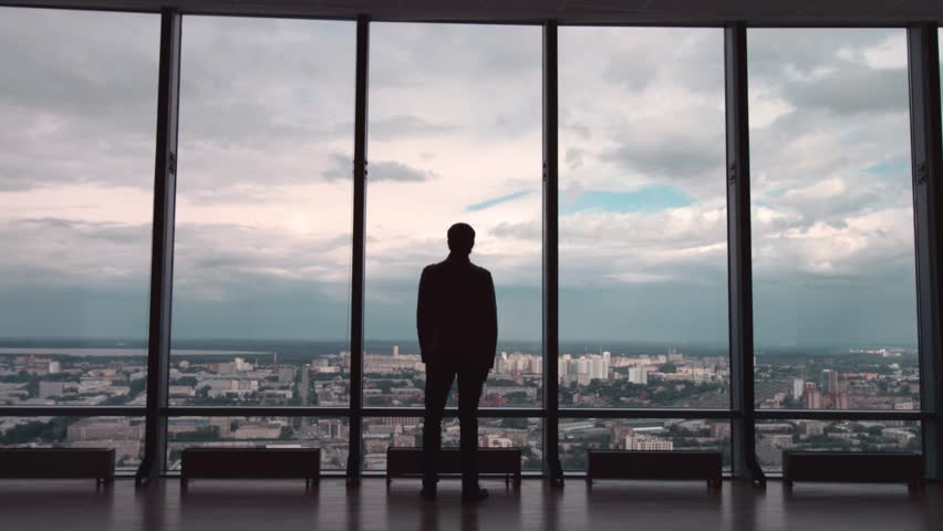 Rear view of man in formal suites who stand in front of panoramic window with city view. a man stands in front of big panoramic wiindow view from back.