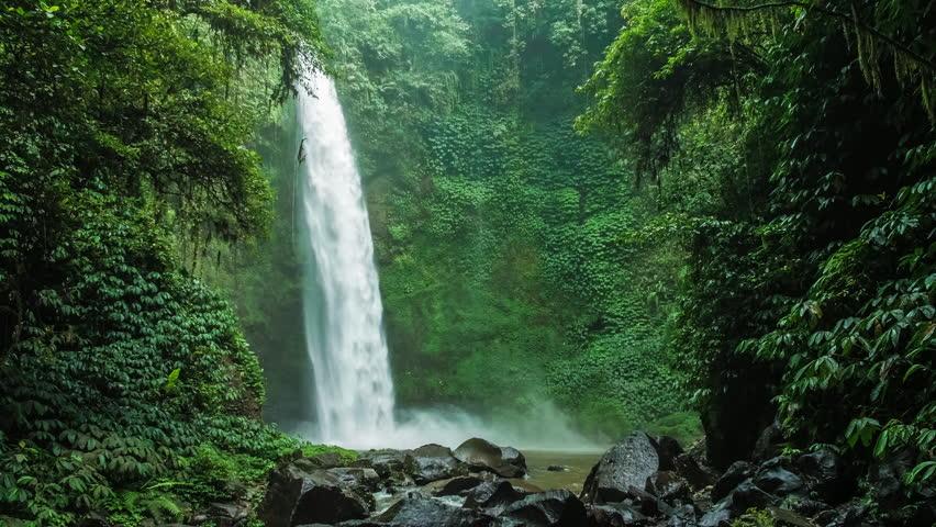 Amazing Nungnung waterfall, Falling water hitting water surface, some huge rocks seeable in front of frame. Lush green leafes is moving from the wind, Bali, Indonesia Royalty-Free Stock Footage #26452013
