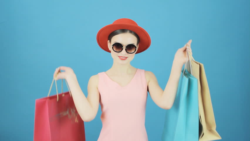 Portrait of Smiling Brunette with Red Hat and Sunglasses on Blue Background in Studio. Happy Woman Holding a Lot of Shopping Colorful Bags. Seasonal Sale Concept.