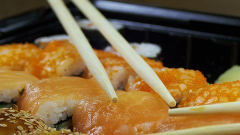 Japanese Sushi Rolls with Chopsticks Rotates. Close-up. Variety of types sushi with Philadelphia cheese, sesame, red caviar, salmon fillets. Set of delicious Japanese sushi rolls.