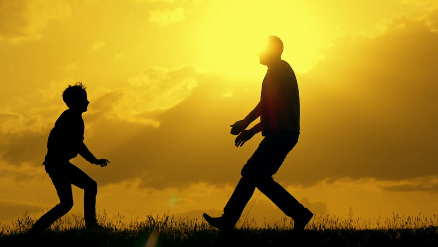 Father and son play in the park during sunset. The concept of a united family. Silhouette on a background of sunset on the sky