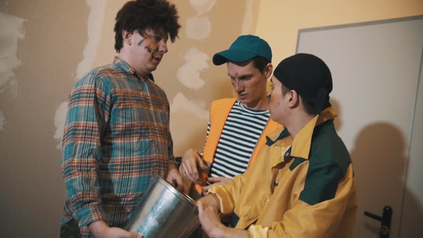 Three middle aged caucasian funny men dressed as dirty workers figuring out what inside tin bucket, laughing #26463995