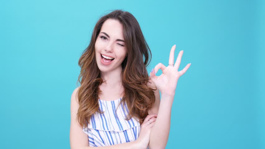 Young cheerful woman winking and showing gesture okay isolated | Shutterstock HD Video #26466179
