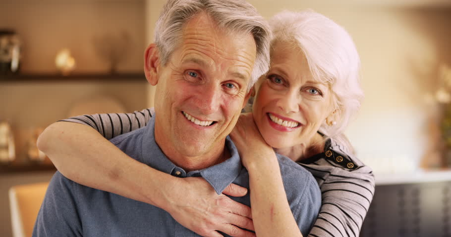 Happy elderly couple sitting at home smiling at camera. Closeup of senior couple smiling. 4k | Shutterstock HD Video #26472596