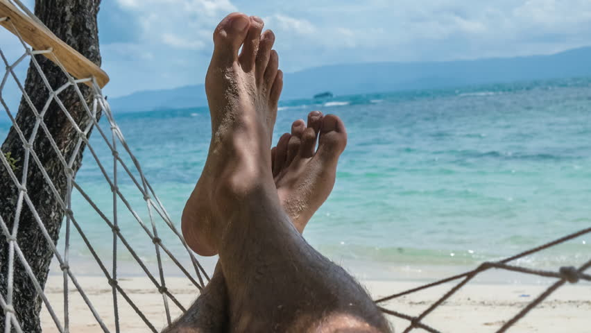 Swinging bare man feet with beach white sand swinging in a hammock on vacation in front of the blue ocean.