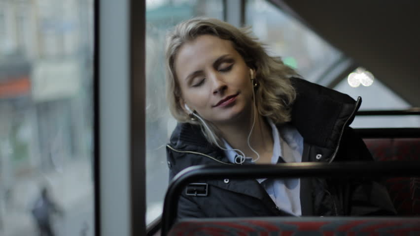 Young blonde girl looking out the window on the bus with phones | Shutterstock HD Video #26477483