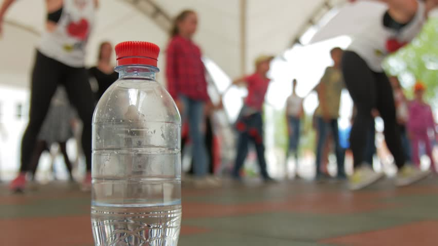 Plastic bottle on the background of a group of people engaged in Zumba fitness. Royalty-Free Stock Footage #26477759