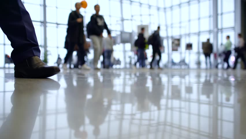 People out of focus walk inside a bright, modern building. Focus in the foreground | Shutterstock HD Video #26497643