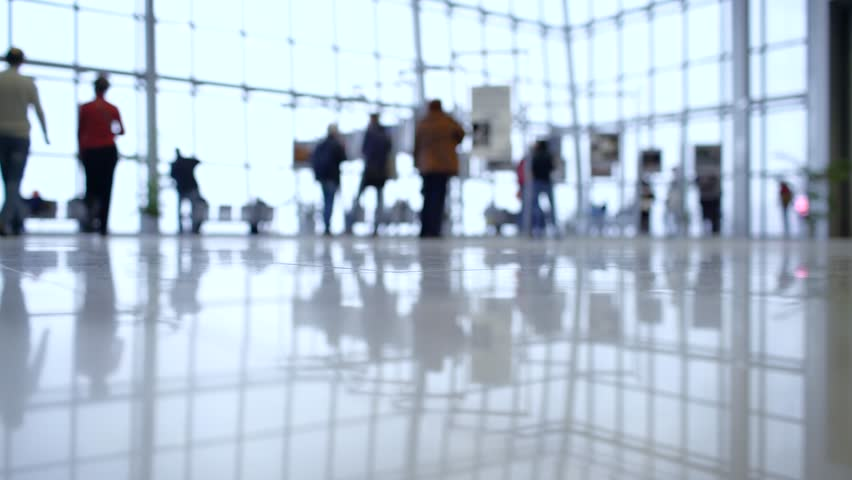 People out of focus walk inside a bright, modern building. Focus in the foreground | Shutterstock HD Video #26497646
