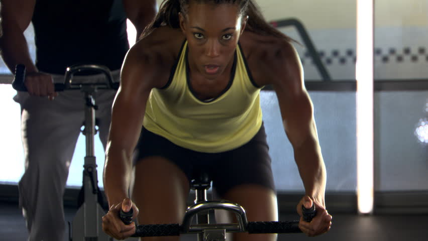 Tilt-up from wheel of stationary bicycle to woman cycling in spinning class Royalty-Free Stock Footage #26500676