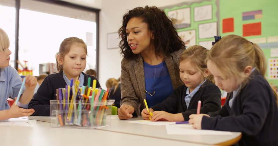 4K Primary school children drawing in the classroom with teacher helping. Slow motion Royalty-Free Stock Footage #26503412