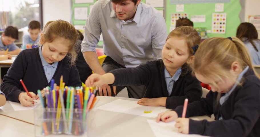 4K Primary school children drawing in the classroom with teacher helping. Slow motion   Shutterstock HD Video #26503424