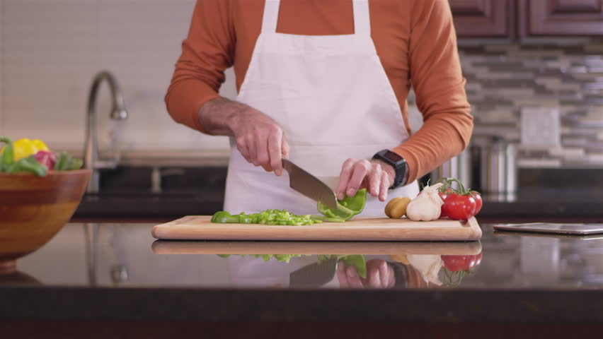 Close up shot of an old chef chopping up a green bell pepper #26505452