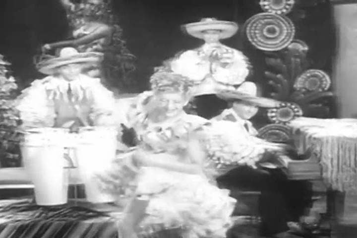 1940s: A woman sings an upbeat Mexican themed or Hispanic ballad in the 1940s soundie.