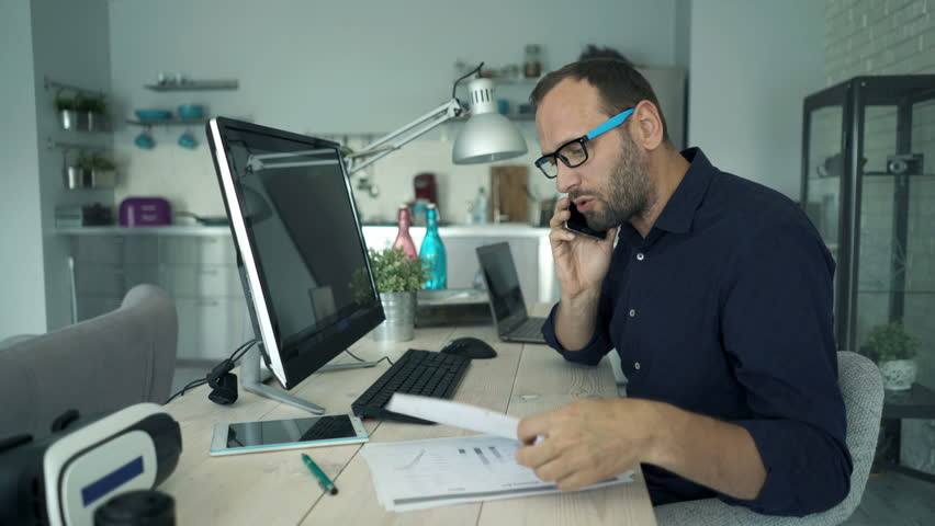 Angry man with documents and pc computer talking on cellphone by table at home    Shutterstock HD Video #26516423