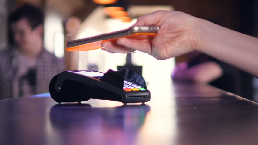 Person using Credit Card Terminal for wireless payment with smartphone. 4K.