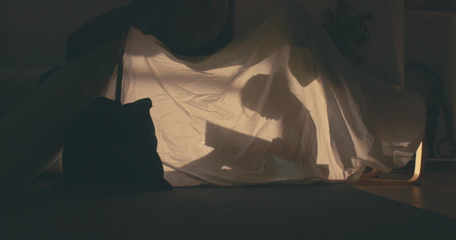 Silhouette of little girl reading a book inside a blanket fort in the evening, lit by a lamp from inside. 4K UHD RAW edited footage