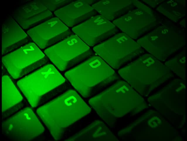 A closeup of a keyboard with green light shinning on it and then it fades to blue.   Shutterstock HD Video #265300