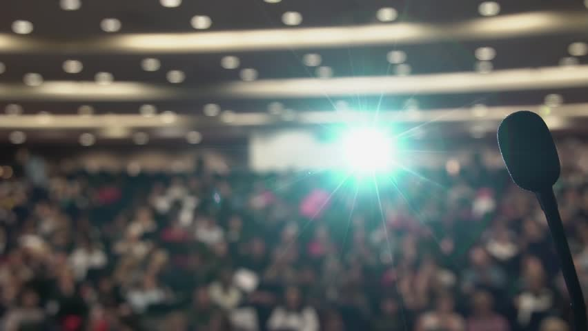 Many people sit in large hall at conference. Projector light via the microphone. Royalty-Free Stock Footage #26534633