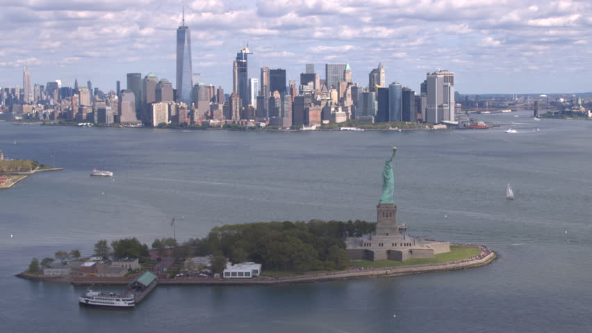 AERIAL ESTABLISHING SHOT: Flying around Lady Liberty statue in front of big New York City skyline. Famous Statue of Liberty standing proudly with New York downtown skyscrapers in the background | Shutterstock HD Video #26546003