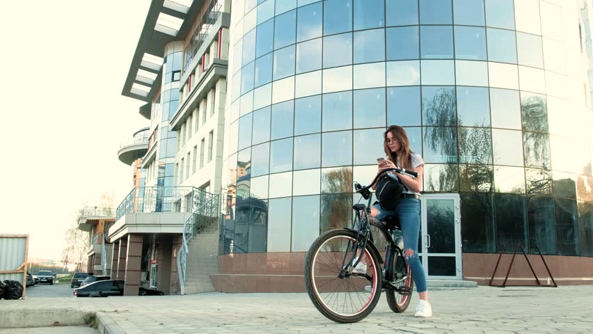 Beautiful woman rides a bicycle near a tall building | Shutterstock HD Video #26551883