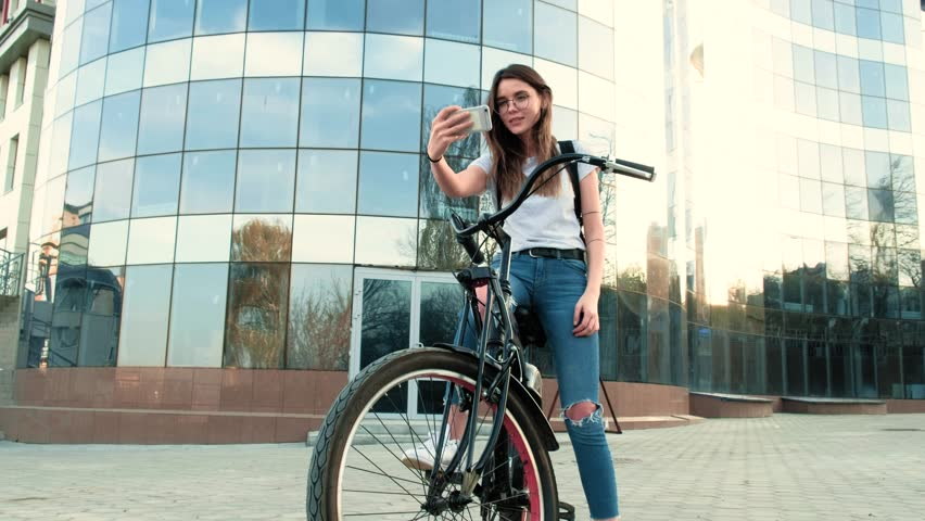 Beautiful woman rides a bicycle near a tall building | Shutterstock HD Video #26551892