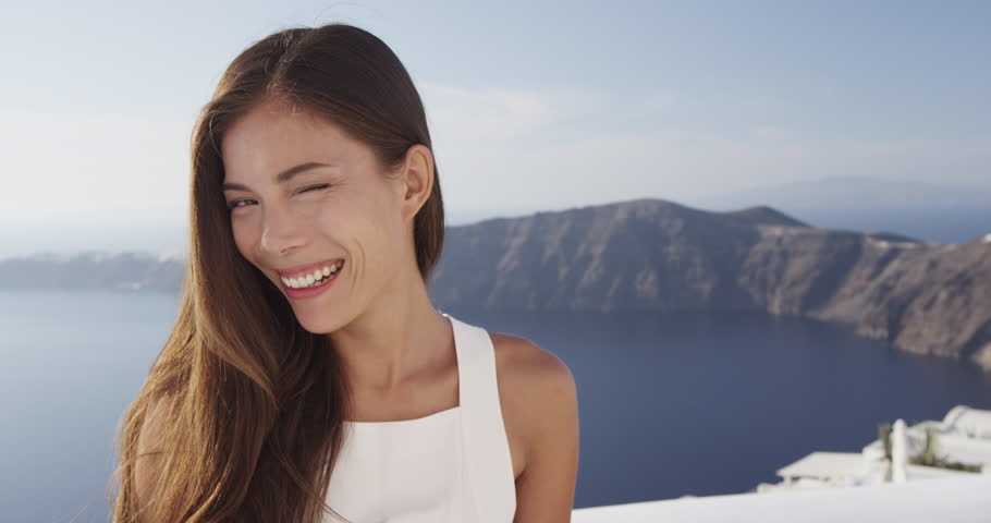 Cute girl laughing and smiling winking and goofing around looking at camera having fun. Portrait of beautiful mixed race Asian Chinese / Caucasian young woman on Santorini, Greece.