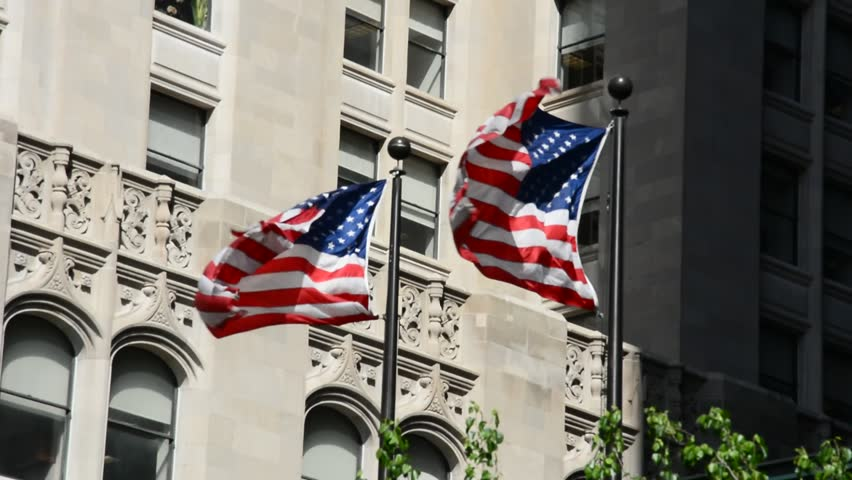 NEW YORK CITY, USA - MAY 4, 2017. Waving American flags with building in the background.