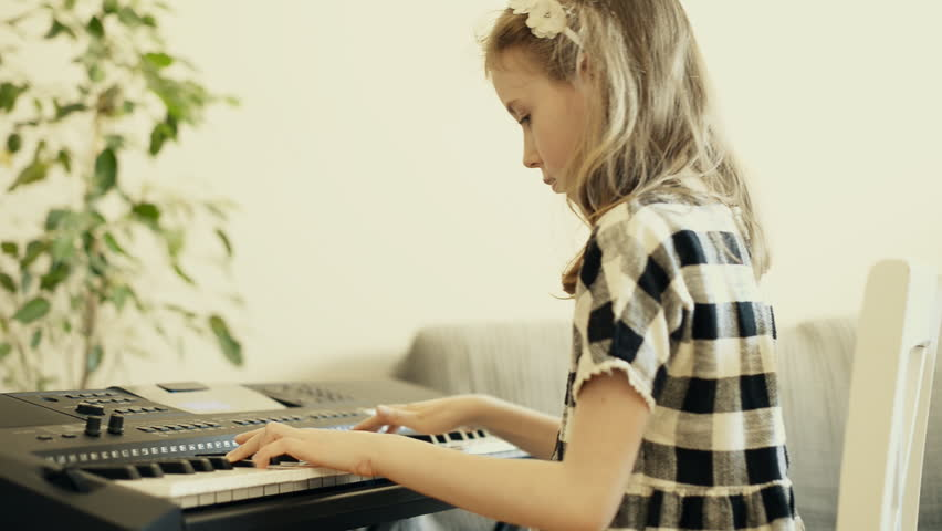 Little girl learning to play the piano.