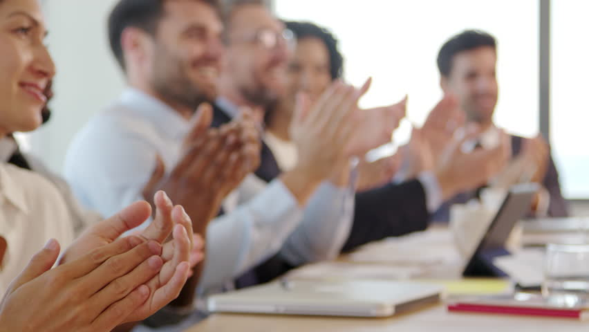 Businesspeople Around Boardroom Table Applaud Presentation