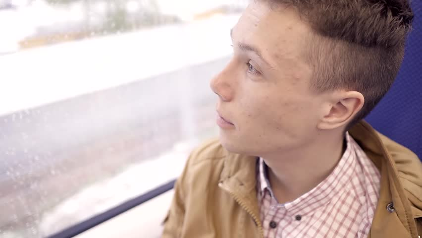 Teen boy with pimples on the face going on the train and looking out the window. Closeup. | Shutterstock HD Video #26609357