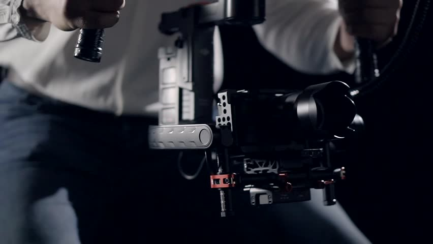 Smooth movement of the camera in the protective cage installed on the stabilizer in the hands of the operator focusing on the screen recorder. #26617319