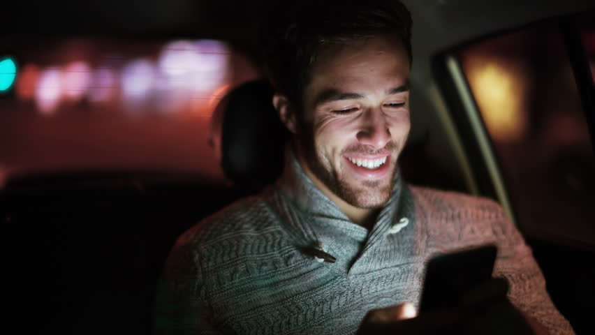 Handsome young man using cell phone in a car. He is texting, checking emails, chats or the news online. Night.