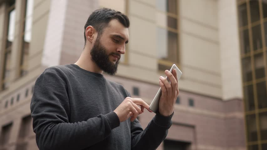 Happy beard young man using tablet computer in the street at sunset | Shutterstock HD Video #26621677