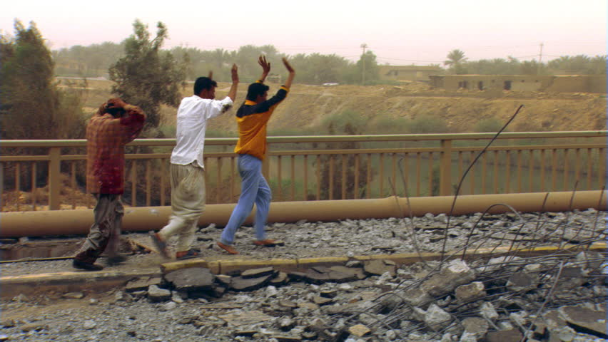Iraqi citizens fleeing across partially destroyed bridge