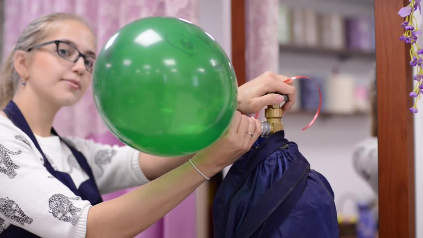 Young girl with glasses inflate the balloons with helium   Shutterstock HD Video #26634769