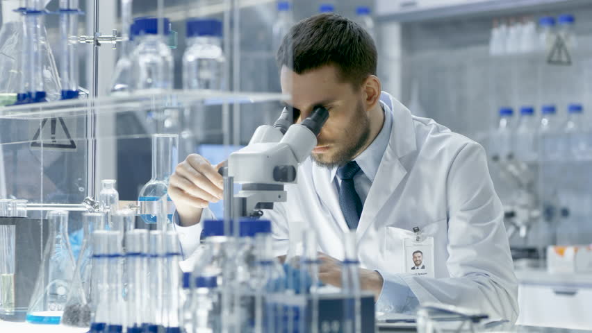Young Male Research Looks at Sample under Microscope then Looks into Camera and Smiles. He's Sitting in a High-End Modern Laboratory with Beakers, Microscope and Working Monitors Surround Him.