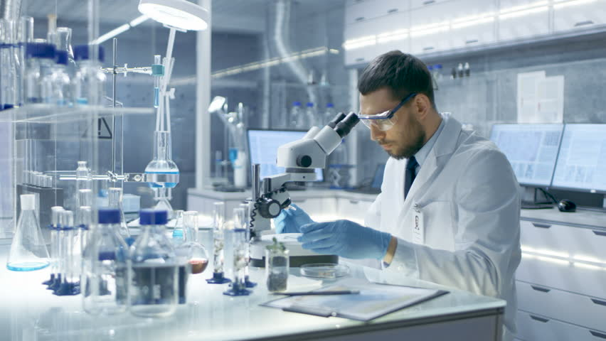 In a Modern Laboaratory Research Scientist Uses Pipette to Drop Substance on a Slider and Examines it Under Microscope. He Then Writes Down His Observations. Shot on RED EPIC-W 8K Helium Cinema Camera | Shutterstock HD Video #26643673