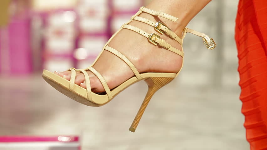 Young Woman Trying On High Heels In Shoe Store