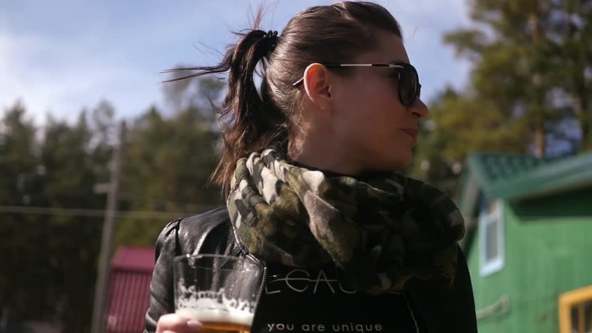 Girl standing on the street against the trees drinking tasty foam beer. slow motion. HD, 1920x1080.